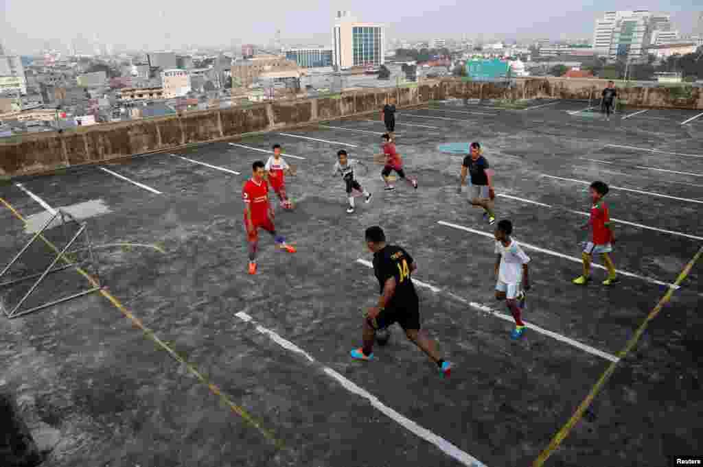 Дети играют в футбол на крыше гаража в Джакарте. Индонезия, 4 мая 2018 года.