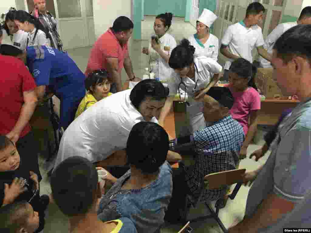 Врачи проводят первичный анамнез людей, поступивших в эвакуационный пункт.