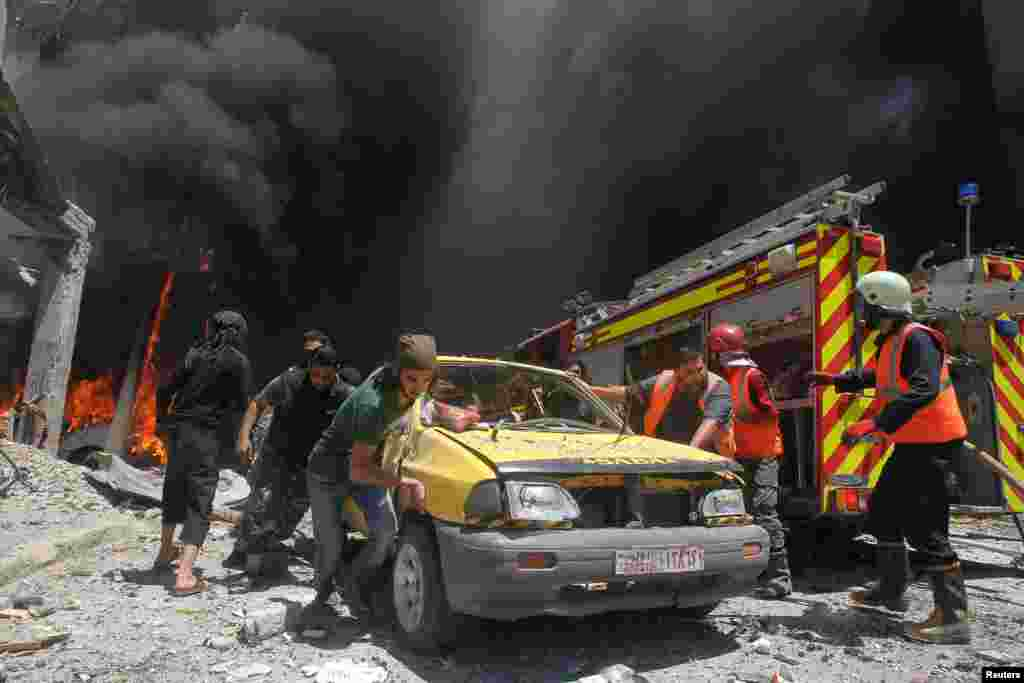 Civil-defense members and rescuers push a car at a site hit by air strikes in Idlib, Syria. (Reuters/Ammar Abdullah)