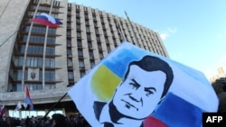 A demonstrator holds a flag with a portrait of ousted Ukrainian President Viktor Yanukovych during a rally of pro-Russia supporters outside the regional government administration building in the center of the eastern Ukrainian city of Donetsk on April 5.