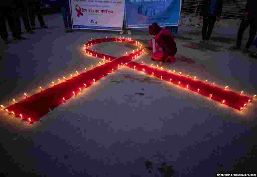 Nepál - Égő gyertyák formázzák meg az AIDS világnapja szimbólumát egy rehabilitációs- és árvaház épülete előtt. A gyertyák a HIV-fertőzésben elhunytak emlékére égtek.
