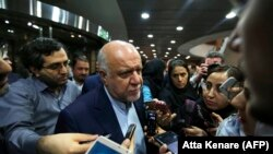 Iranian Oil Minister Bijan Namadar Zanganeh talks with Iranian journalist after signing an oil field agreement in Tehran, March 14, 2018