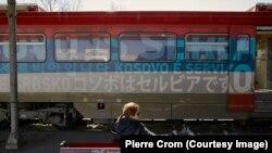 Пассажир ждет отправления поезда, украшенного сербскими флагами и расписанного лозунгами «Косово – это Сербия» на 20 языках. Белград, Сербия, март 2018 года