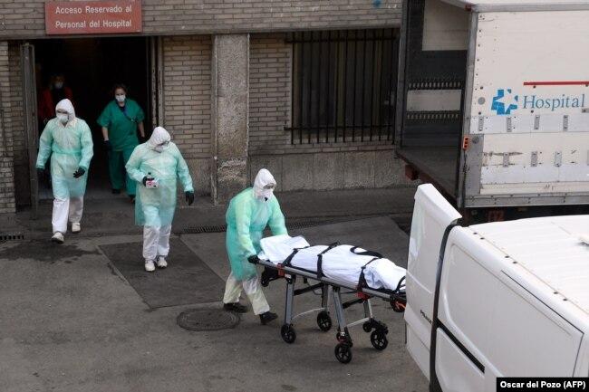 ესპანეთი, სამედიცინო პერსონალს კორონავირუსით გარდაცვლილი ადამიანი მიჰყავს, 25 მარტი.