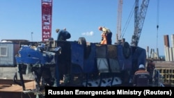 Автобус, вытащенный из воды, куда он упал с рабочими со строящегося пирса на Таманском полуострове. Краснодарский край, 25 августа 2017 года.