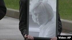 Anna Politkowskaýanyň portretini göterip barýan adam.