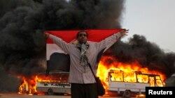 متظاهر أمام مقر الاخوان المسلمين والنيران تتصاعد من باصين خلفه