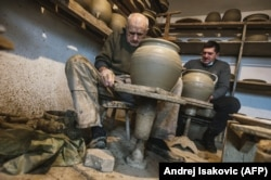 Goran Savic (right) and his 91-year-old grandfather, Milan, shape clay cooking pots in the village of Zlakusa, in central Serbia, on December 28.
