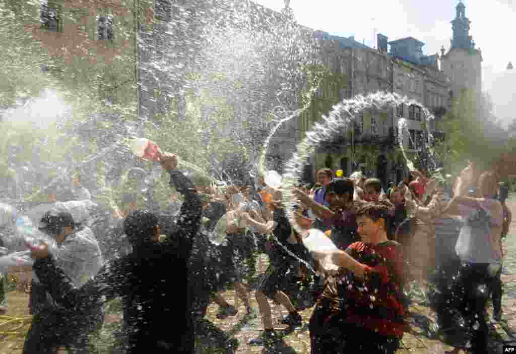 "People spray water on one another in the western Ukrainian city of Lviv in a bit of traditional Easter horseplay on ""Wet Monday."" (AFP/Yuriy Dyachyshyn)"