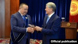Ex-President Almazbek Atambaev (right) bestows an award on adviser Ikramjan Ilmiyanov in November 2017.