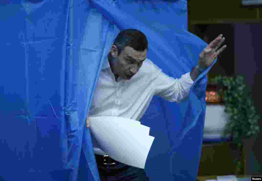 Heavyweight boxing champion and UDAR (Ukrainian Democratic Alliance for Reform) party leader Vitali Klitschko leaves a booth before casting his vote at a polling station in Kyiv.