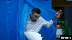 Виталий Кличко покидает кабинку для голосования на избирательном участке в Киеве. 25 мая 2014 года.