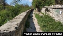 Через бетонированную дорожку проросла трава, подпорная стенка разрушается