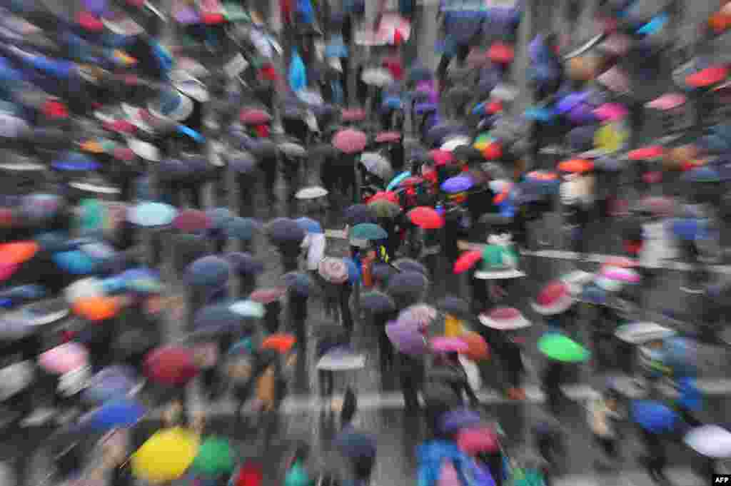 People wait in the rain at St. Peter's Square for the smoke announcing the result of the conclave at the Vatican. A new pope, Pope Francis, was elected on March 13. (AFP/Tiziana Fabi)