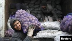 Трудовые мигранты из Центральной Азии разгружают грузовик с картофелем в Москве.