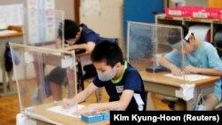 У Японії власна система: шкільний рік закінчується в кінці березня, а новий починається вже через тиждень, на початку квітня, але є довші літні канікули в серпні і зимові наприкінці грудня – на початку січня. На фото: початкова школа, з масками і захисними щитками, в місті Фунабасі, Японія, 16 липня 2020 року