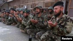 Afghan National Army soldiers pray for their fallen colleagues.