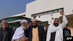 Pakistani Minister for Religious Affairs Sardar Yousuf (C) and lawmakers chant slogans against the printing of satirical sketches of the Prophet Muhammad.