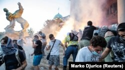 Demonstrators clash with police officers in front of the parliament building in Belgrade.