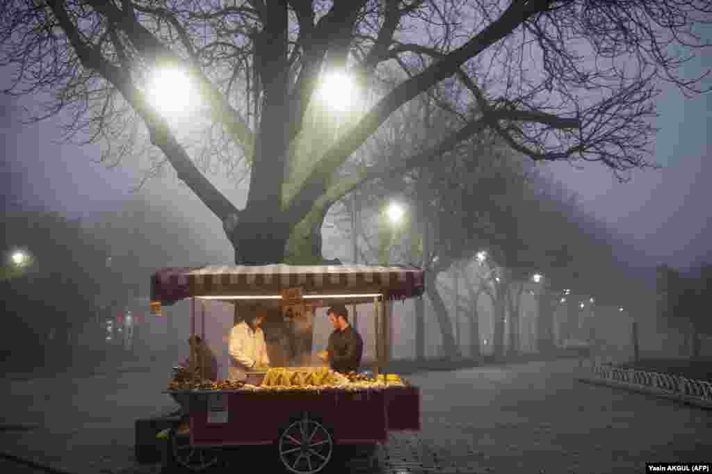 Street vendors sell corn on Sultanahmet Square near the Blue Mosque on a foggy day in Istanbul. (AFP/Yasin Akgul)