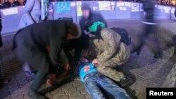 Люди надають допомогу потерпілому після дій «Беркуту». Київ, 30 листопада 2013 року