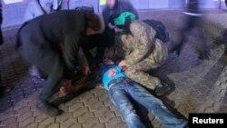 Милиция операциясы кезінде зарап шеккен адамға жәрдем көрсетіп жатыр. Тәуелсіздік алаңы, Киев, 30 қараша 2013 жыл.