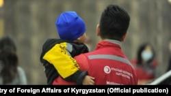 Қизил ярим ой жамияти ходими Ироқдан Қирғизистонга қайтарилган болалардан бирини кўтариб турибди, 2021 йил 16 марти