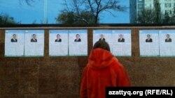 Өзбекстан президенттігіне кандидаттардың сайлауалды материалдарына қарап тұрған әйел. Ташкент, 21 қараша 2016 жыл.