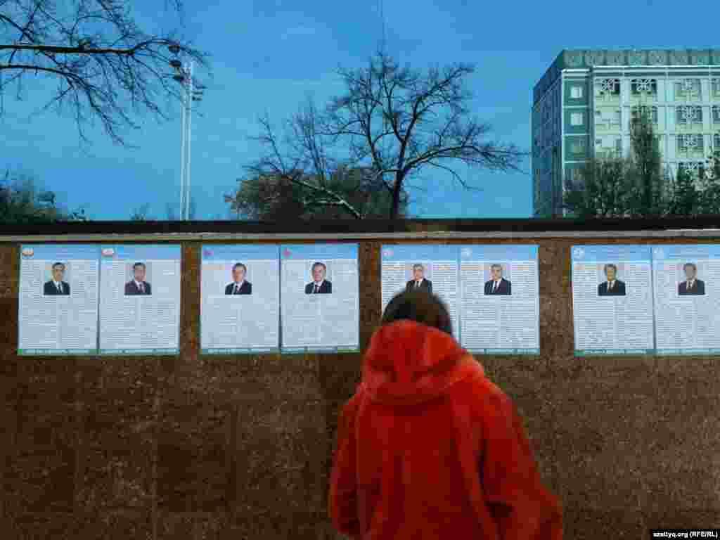 Женщина стоит перед щитом, на котором размещены предвыборные материалы кандидатов в президенты Узбекистана. Ташкент, 21 ноября 2016 года.