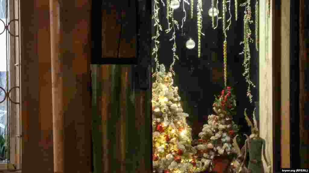 Витрины магазинов, кафе и различных заведений в городе изобилуют гирляндами и елками
