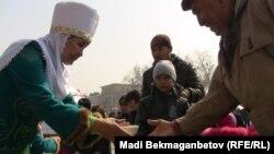 Женщина в национальном казахском костюме подает мужчине «наурыз-коже», традиционное блюдо во время празднования Наурыза.