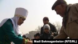 Женщина в национальной казахской одежде подает мужчине чашку с наурыз-коже. Алматы, 21 марта 2011 года.