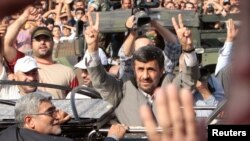 Iranian President Mahmud Ahmadinejad flashes victory signs as he greets Lebanese supporters upon his arrival in Beirut on October 13.