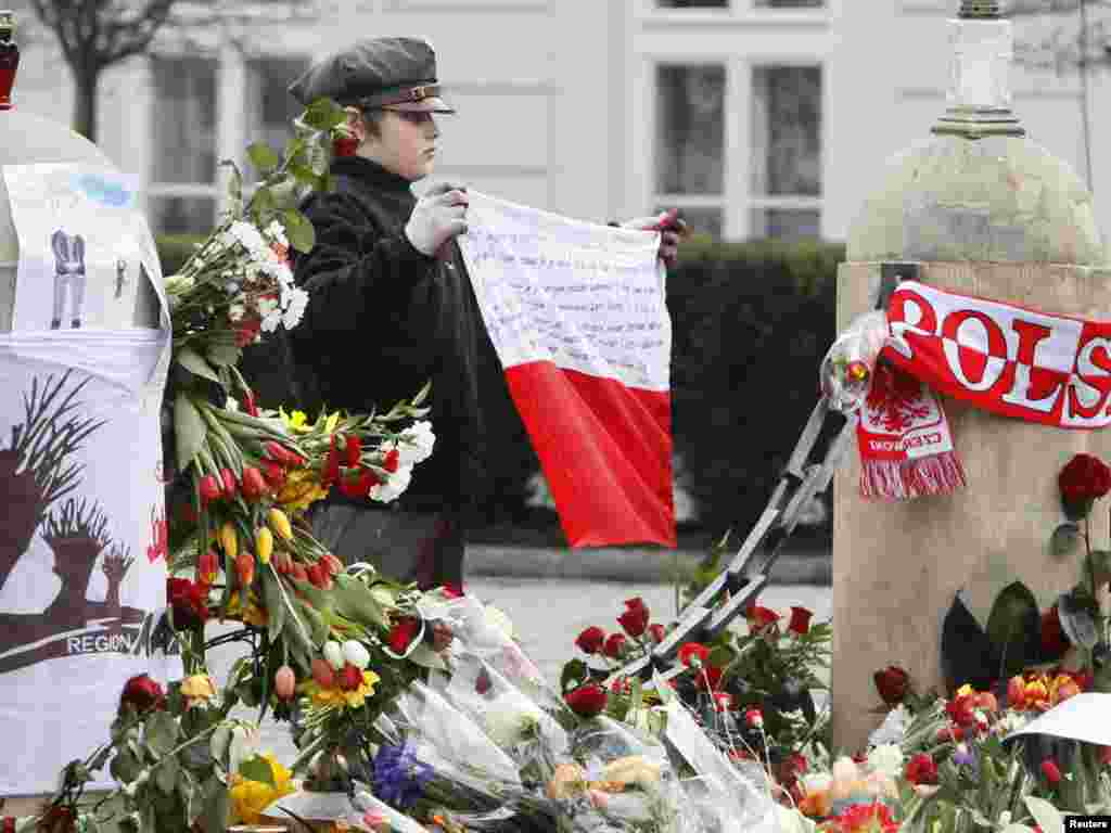 A scout holds a Polish national flag in front of the presidential palace.
