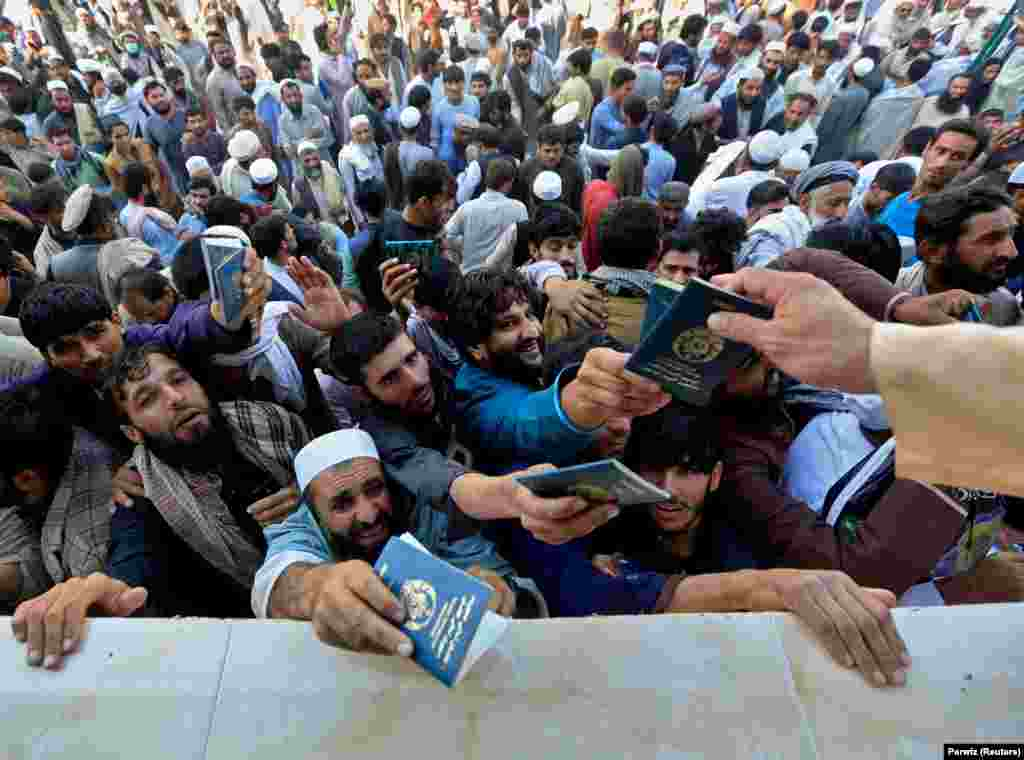 Afghan men wait to collect tokens needed to apply for a Pakistani visa at Islamabad's consulate in Jalalabad. (Reuters/Parwiz)