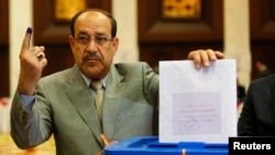 Iraqi Prime Minister Nuri al-Maliki votes during parliamentary elections in Baghdad on April 30.