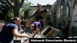 Residents remove debris outside a house that locals said was damaged during recent shelling in the rebel-controlled city of Donetsk on June 17.