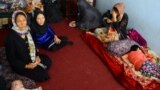 An Afghan family sits in an International Organization for Migration transit center in the western Herat Province after returning from Iran on August 2.