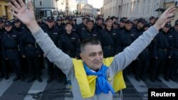 Чоловік з українським прапором на плечах стоїть біля кордону ОМОНу під час антивоєнної демонстрації в Москві, 21 вересня 2014 року