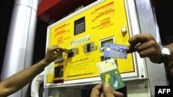 Iranians show their rationing cards at a gas station