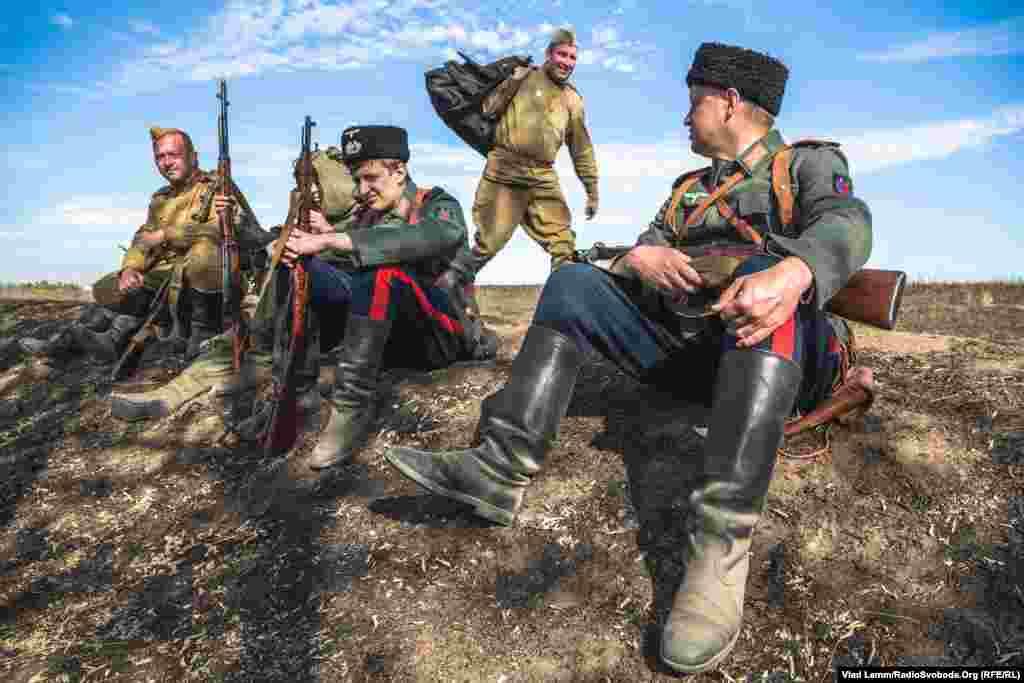 Реконструктор у формі російських «казаків», які воювали на стороні нацистів, поряд із «радянськими бійцями»