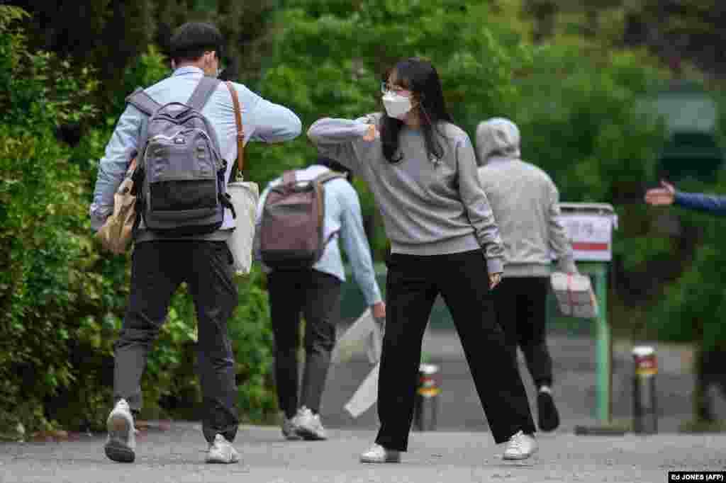 Працівниця середньої школи Кйонбок у Сеулі вітається з учнями, які йдуть на заняття, 20 травня 2020 року. Сотні тисяч південнокорейських учнів повернулися до шкіл, які почали відкриватися після більш ніж двомісячного карантину, запровадженого через спалах коронавірусної хвороби
