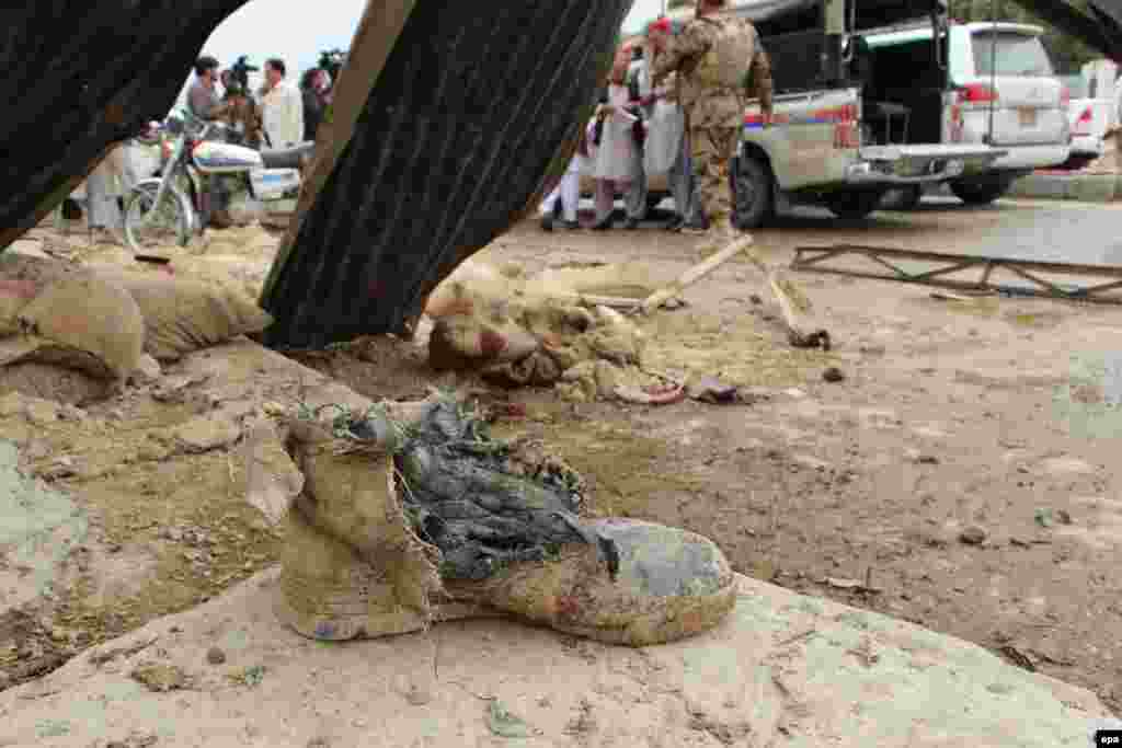 The shoe of one of the victims lies on the ground as Pakistani security officials inspect the site of a bomb blast that targeted a police checkpoint in Quetta on May 10. (epa/Jamal Taraqai)