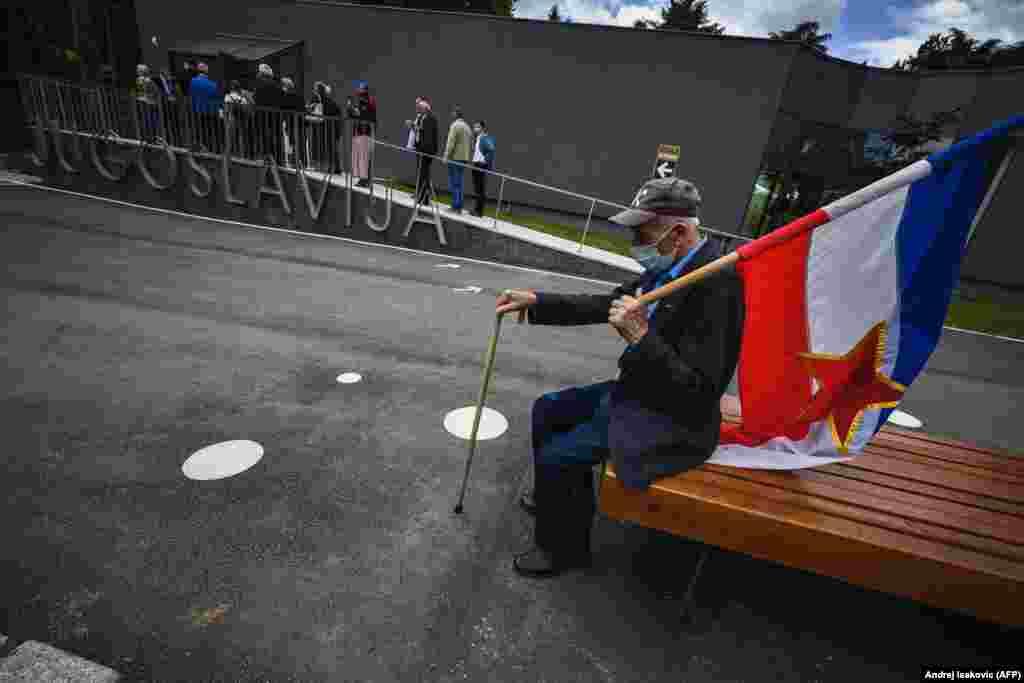 Шанувальник тримає прапор колишньої Югославії, сидячи на лавці перед меморіальним комплексом, який присвячений покійному колишньому президенту Югославії Йосипу Броз Тіто, в Белграді. Групи людей сходилися до меморіалу Тіто, щоб відзначити його 128-й день народження (AFP/Andrej Isakovic)