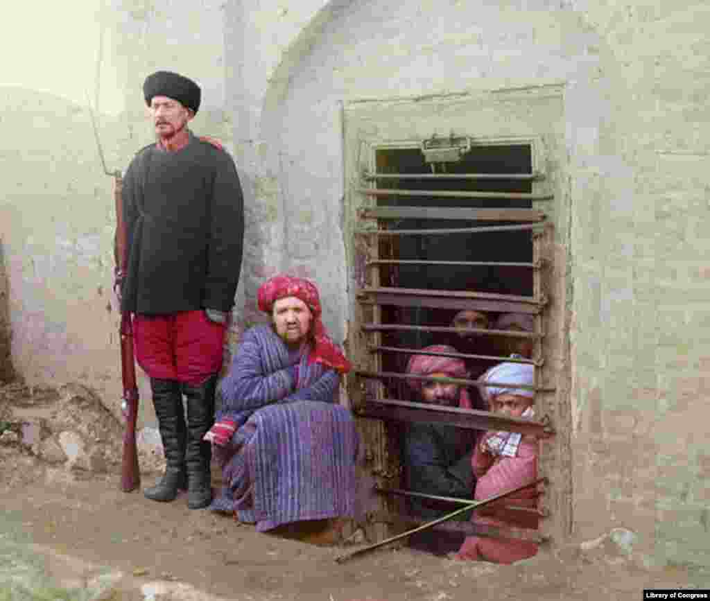 Inmates of a zindan -- a Central Asian prison -- are guarded by a man with a Russian-style uniform and boots.