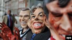 Лондондо коомдук угуу башталганда эшикте пикетчилер Жорж Буш, Тони Блэр, Гордон Браундун канга боелгон маскаларын кийип турушту. 24-ноябрь, 2009-ж.