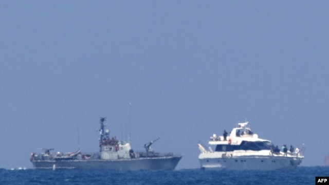 An Israeli military vessel (left) escorts one of the boats in a Gaza-bound aid convoy with Israeli troops on board to the southern Israeli port of Ashdod.