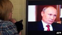 A woman looks at Russian President Vladimir Putin on screen as she watches the documentary Crimea: Path To The Homeland on March 15.