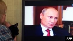 """""""Крым. Мекенге карай жол"""" деген тасмада сүйлөп жаткан Путинди көрүп отурган аял"""