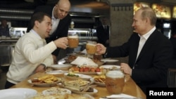 Then-President Dmitry Medvedev (left) and then-Prime Minister and President-elect Vladimir Putin toast with beers at a casual lunch meeting on May 1.